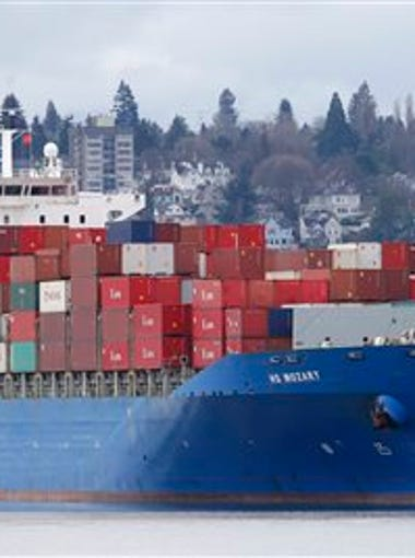 In this Feb. 20, 2015 file photo, a sailboat moves past the 925-foot long HS Mozart cargo ship, operated by the German shipping company Hansa Shipping, anchored in Commencement Bay near the Port of Tacoma, Wash.   The U.S. trade deficit increased in June as solid consumer spending pulled in more imports, while the strong dollar restrained exports.  The Commerce Department says the trade gap jumped 7 percent to $43.8 billion in June, up from $40.9 billion in May. Imports increased 1.2 percent to $232.4 billion, while exports edged lower to $188.6 billion from $188.7 billion.