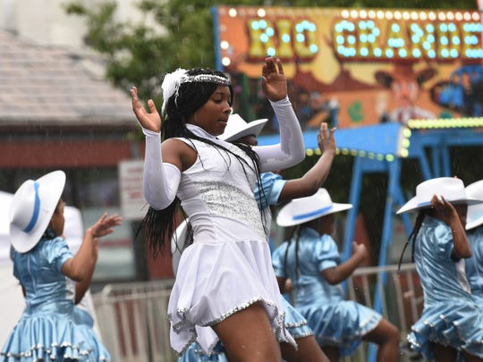 Ashiiya Pleasant (center) of The Hillside Showtime Strutters performs with the rest of the group in the rain during the Juneteenth celebration on Saturday in Englewood.