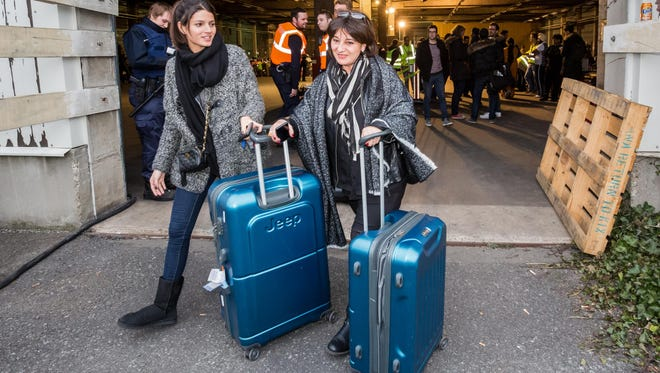 People pick up luggage they had to leave behind during Tuesday's terrorist attack on Brussels Airport, in a warehouse near the airport.