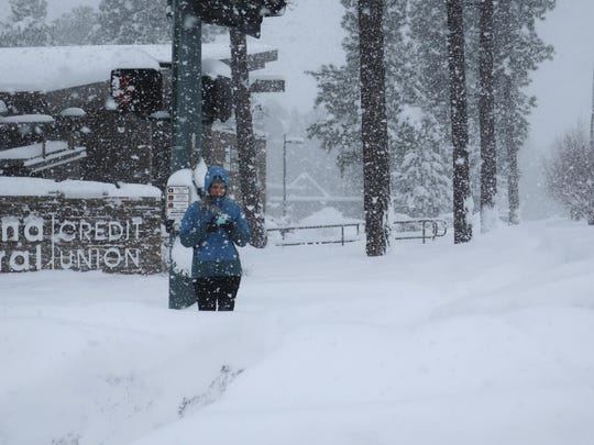 A pedestrian waits for a crossing signal in Flagstaff, Arizona, on Feb. 21, 2019. Schools across northern Arizona canceled classes and some government offices decided to close amid a winter storm that's expected to dump heavy snow in the region.