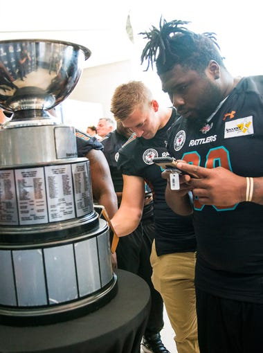 Arizona Rattlers players looks at the United Bowl trophy during a press conference at Talking Stick Resort Arena in Phoenix, Ariz. July 12, 2017. The Arizona Rattlers were celebrating their United Bowl championship.