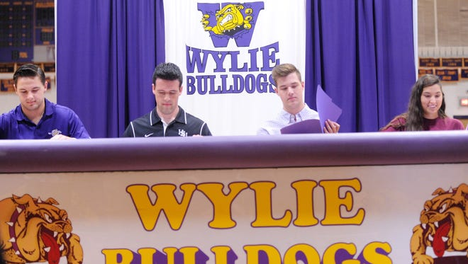 Four Wylie athletes participated in a signing ceremony at Bulldog Gym on Tuesday. From left, Ryan Hamar, Kyle Roberts, Dylan Isenhower and Kaitlyn Hathorn made their college commitments.