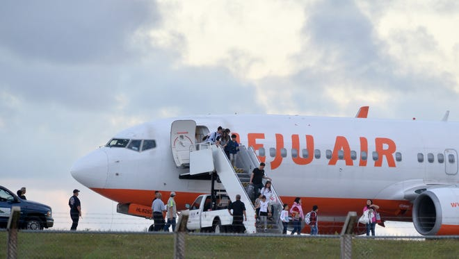 In this file photo, passengers deplane a Jeju Air plane parked on the runway at A.B. Won Pat Guam International Airport.