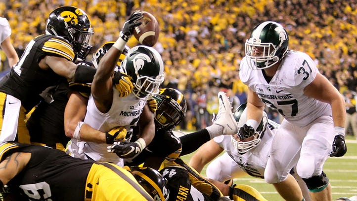 The shocker: Michigan State players go wild after Jalen Watts-Jackson's winning touchdown on the final play of the game stuns the Wolverines, 27-23, at Michigan Stadium on Oct. 17.