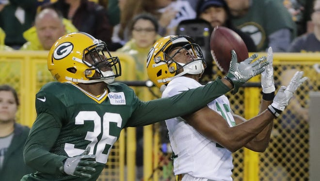 Green Bay Packers wide receiver Malachi Dupre catches a pass over cornerback LaDarius Gunter (36) during Family Night at Lambeau Field.