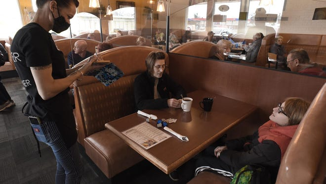 Melissa Fox, a waitress at R Diner in Monroe, takes the order of Anna Steele and her son, Cameron, 11, Monday morning. Like other restaurants statewide, the diner will soon shift to take-out and delivery only as a result of an order issued by the Michigan Department of Health and Human Services.