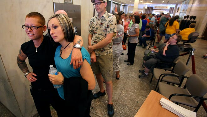 Traci and Leanne van de Bossche wait to enter the Marion County Clerk's office to receive their marriage license on June 25.