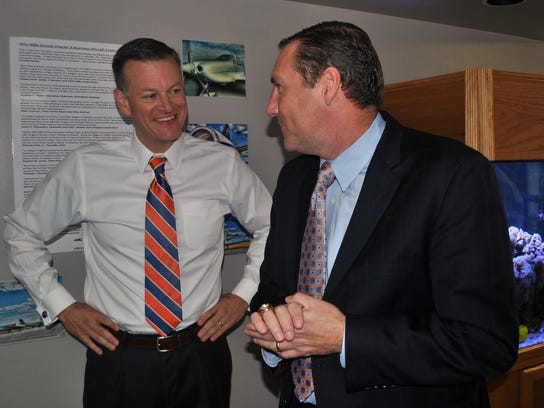 University of Florida athletic director Scott Stricklin, left, smiles as he talks to Florida's new NCAA college football coach Dan Mullen after Mullen arrived at the airport in Gainesville, Fla., Monday, Nov. 27, 2017. (AP Photo/Mark Long)
