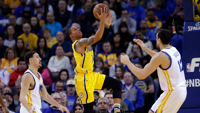 Indiana Pacers' Joe Young, center, drives to the basket past Golden State Warriors' Klay Thompson, left, and Andrew Bogut during the first half Jan. 22, 2016, in Oakland, Calif.