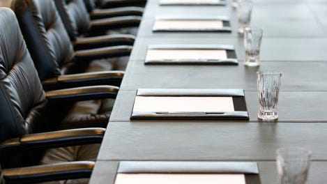 The boardroom table is set for a meeting