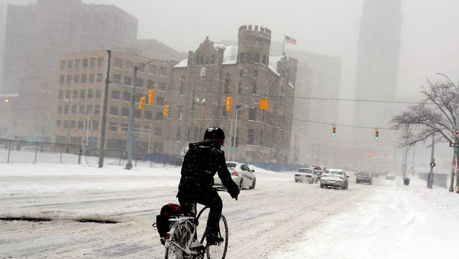 A bicyclist navigates Grand River Avenue in Detroit approaching downtown Detroit  during a morning snow storm that hit the area on Feb. 5, 2015. An event to be held Tuesday will discuss the impact extreme weather and climate change have on small businesses.