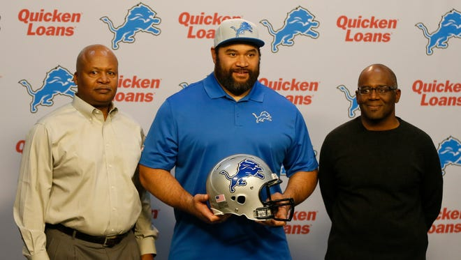 Detroit Lions head coach Jim Caldwell, left, and general manager Martin Mayhew, right, pose with new defensive tackle Haloti Ngata on March 10, 2015.