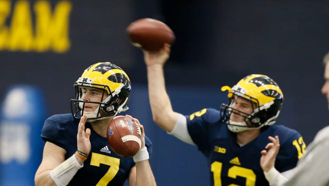 Michigan quarterbacks Shane Morris, left, and Alex Malzone, right, during football practice on Thursday, March 19, 2015 in Ann Arbor.