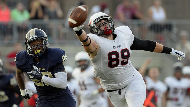 St. Cloud State tight end Grant Thayer (89) tries to reel in a pass under pressure from Concordia-St. Paul's Breon Hoosier (20) in the first half Thursday night at Husky Stadium.