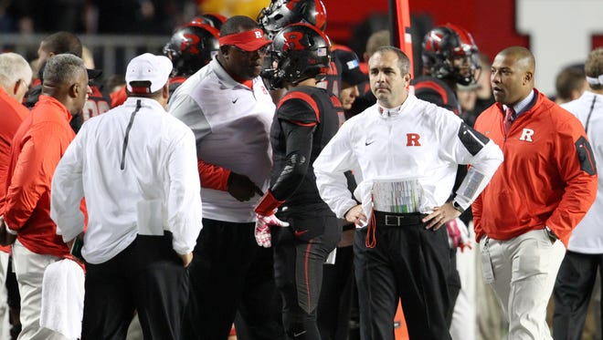 Rutgers interim head coach Norries Wilson speaks with quarterback Chris Laviano on the sideline.