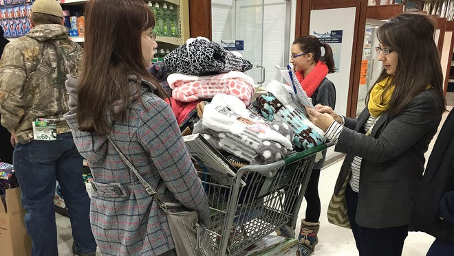 Shoppers wait in line to check out on Nov. 27 at Menards in Waite Park.