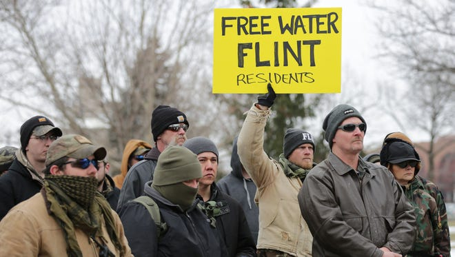Troy Wright , 45, of Flint Township holds a sign with fellow members of the Genesee County Volunteer Militia at a water rally at Flint City Hall on Sunday, Jan. 24, 2016.