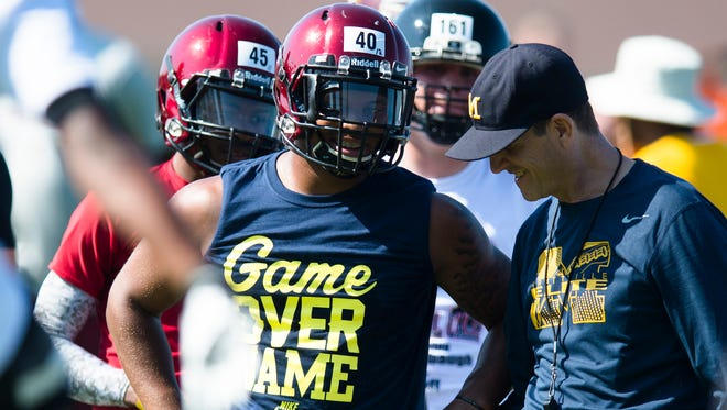 Michigan football coach Jim Harbaugh, right, talks to Prattville running back Kingston Davis during a satellite camp June 5, 2015, at Prattville High School in Prattville, Ala.