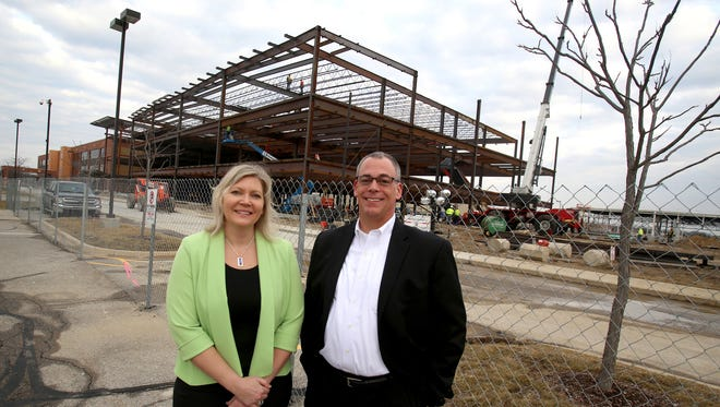 Deb Schroeder and Robert Young, both from Toyota, are in front of the expansion of the Toyota Technical Center in York Township.