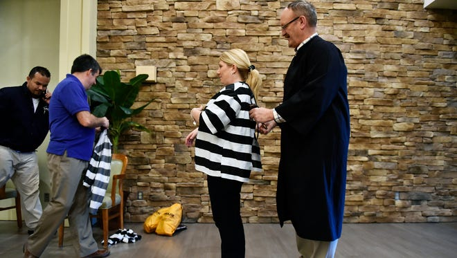 Wyndham Garden York guest service agent Sarah Copp, center, is helped into her 'jailbird' shirt by 'judge' Don Dull of Manchester Township during the Muscular Dystrophy Association's Lock-Up fundraiser at the Wyndham Garden York hotel in West Manchester Township. The money raised during the event will help support the Muscular Dystrophy Association.