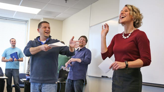 Julie Wright (far right), the director of human resources at Royal United Mortgage, laughs as she is introduced during a training class.