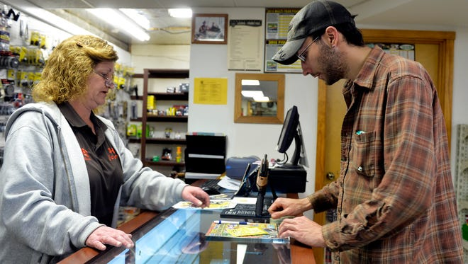 In this 2015 file photo, Hake's Sporting Goods co-owner Janelle Shannon, left, directs Timothy Gile of Windsor Township to sign his new fishing license in Wrightsville.