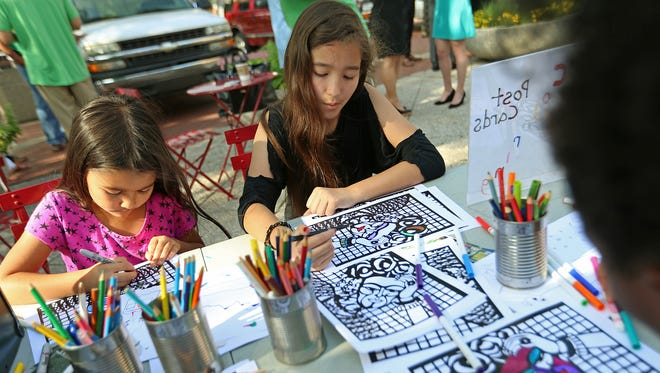 From left, Inori Ogawa, 6, and Himiko Ogawa, 11, color pictures of Frida Kahlo during Placemaking Day in City Market's east plaza, Indianapolis, Wednesday, July 13, 2016. Placemaking Day encourages active use of spaces such as Market Street and Monument Circle downtown.