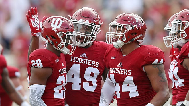 Indiana Hoosiers defensive back A'Shon Riggins (28),  defensive lineman Greg Gooch (49) and  linebacker Marcus Oliver (44) celebrate a quarterback sack against Ball State, turning possession over to Indiana, during second-quarter action at Indiana University's Memorial Stadium in Bloomington on Saturday, Sept. 10, 2016.