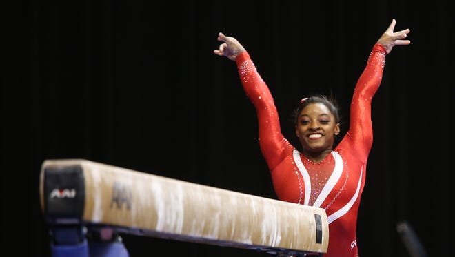 FILE – Simone Biles beams after dismounting the balance beam during the P&G Championships at Bankers Life Fieldhouse, Aug. 15, 2015.