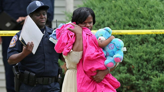 A victim's assistant with the  Indianapolis Metropolitan Police Department carries an unharmed infant girl from an apartment on Admar Court, where three people were found fatally shot on July 22, 2016.