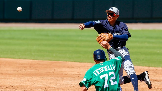 Mar 17, 2017; Lakeland, FL, USA; Yankees infielder Ronald Torreyes throws to first for the double play as the Tigers' Dominic Ficociello slides into second base in the second inning at Joker Marchant Stadium.