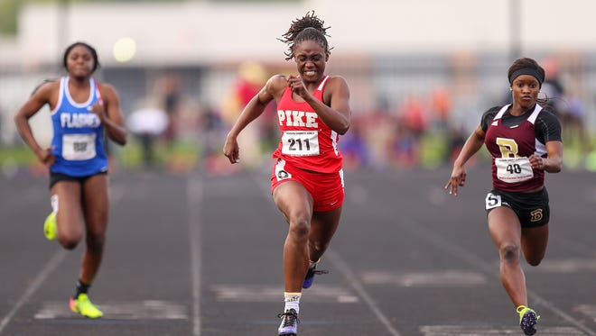 Center, Pike senior Lynna Irby places first in the 100 meter dash in 11.74, as opponents trail behind, left, Frankin Central freshman Alexus Mobley and, right, Brebeuf sophomore Semira Killebrew, during the Marion County girls track and field championship at North Central High School, Indianapolis, Tuesday, May 9, 2017.