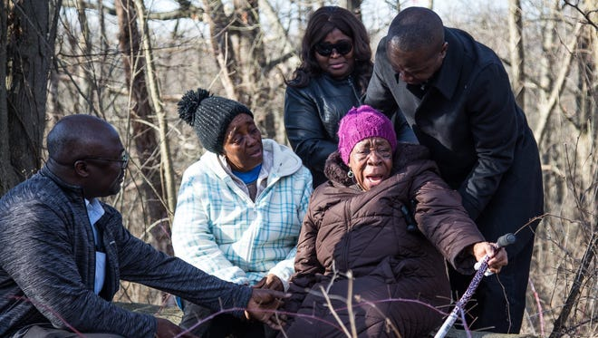 In this Sunday, March 11, 2018, photo, Najah Konney, second from left, sits with others as friends and family gather at the site where the body of her niece Mujey Dumbuya, 16, was found in Kalamazoo, Mich.