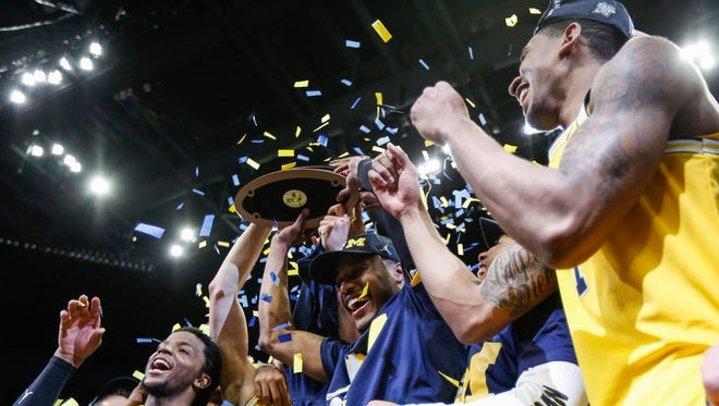 Michigan players celebrate as they raise the West Region championship trophy Saturday night at Staples Center in Los Angeles.