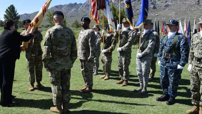 US Army Col. Christopher Ward receives the colors from Brenda Lee McCullough, director of the U.S. Army Installation Management Command, Readiness, signifying his new role as garrison commander at White Sands Missile Range.