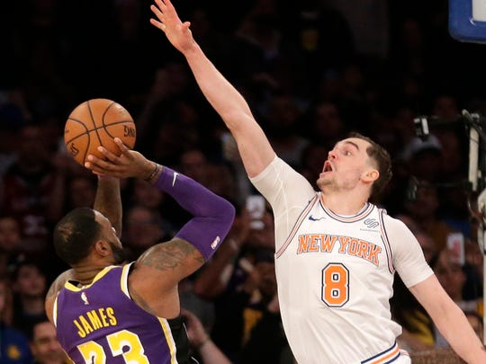 New York Knicks' Mario Hezonja (8), center, blocks what could have been the winning shot by Los Angeles Lakers' LeBron James, left, during the second half of the NBA basketball game, Sunday, March 17, 2019, in New York. (AP Photo/Seth Wenig) ORG XMIT: NYSW107