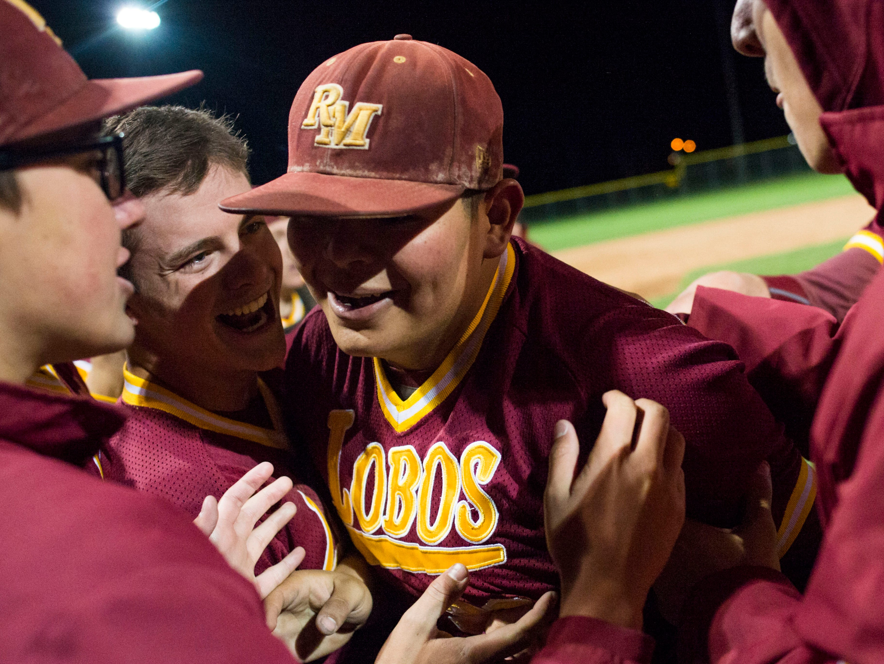 Austin Alarid of Rocky Mountain High School is mobbed by his teammates after the Lobos defeated Fort Collins 7-5 at City Park field Tuesday, April 26, 2016. Alarid struck out all seven batters he faced in the final innings of the game.