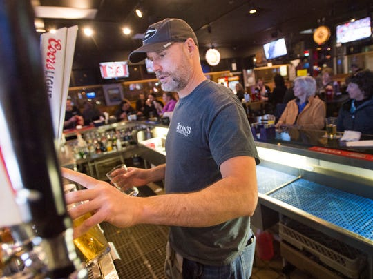 Kent Randle pours beer for the bar crowd at Ryan's Sports Grill on Harmony Road Thursday, January 26, 2017.