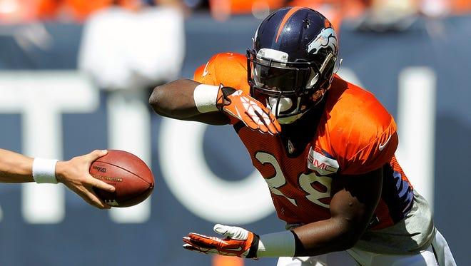 Denver Broncos running back Montee Ball takes a handoff before the start of the NFL Broncos Summer Scrimmage at Sports Authority Field at Mile High on Aug. 2, 2014, in Denver.