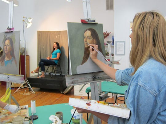 Adult students at work in a portrait painting class