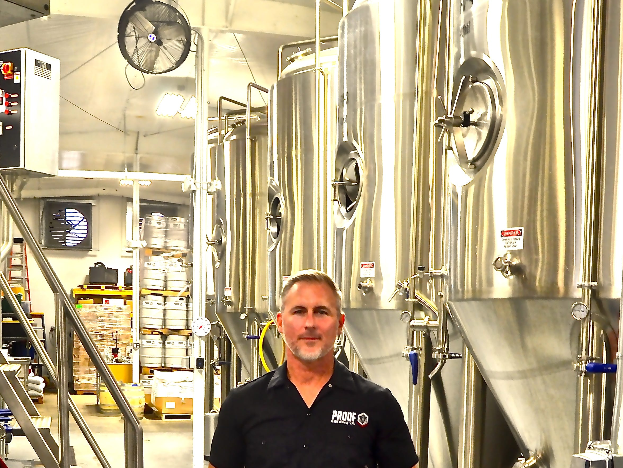 Bryan Burroughs stands amidst the brewing tanks at