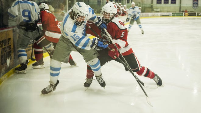 CVU's Charlie Bernicke (5) battled for the puck with South Burlington's Dylan LeClair (16) during the boys hockey game between the Champlain Valley Union Redhawks and the South Burlington Rebels at Cairn's Arena on Wednesday night February 3, 2016 in South Burlington.