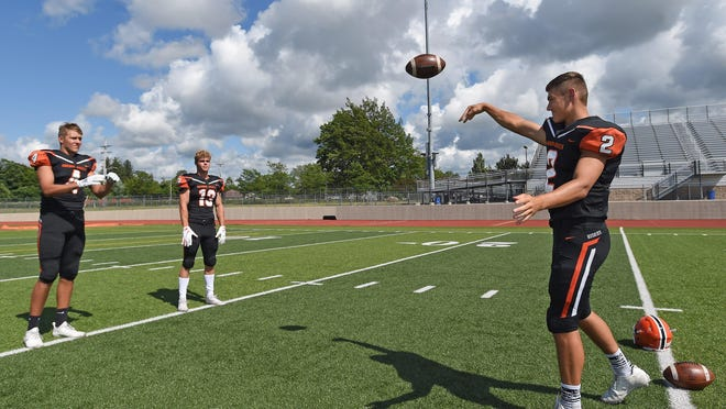Harbor Creek quarterback Casey Smith, right, throws a pass to his twin brother Cody Smith, left, as Marrick Bauer, watches at practice July 13.