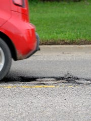 A car drives over a pothole on Aurelius Road Tuesday, April 26, 2016, in Lansing. Cars drive down Michigan Avenue Tuesday, April 26, 2016, over a particularly patchy and pothole-ridden section. MSU researchers are working with the Michigan Department of Transportation to find a better way to set seasonal road restrictions on roads.