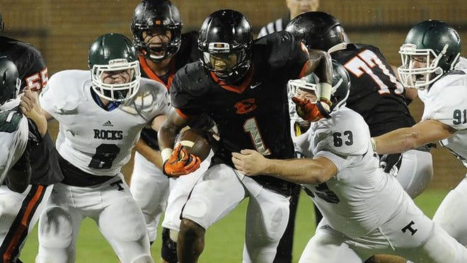 Ensworth's Rico McGraw (1) battles for yards against a host of Trinity Christian defenders during the second half at Ensworth Friday, Aug. 22, 2014 in Nashville, TN