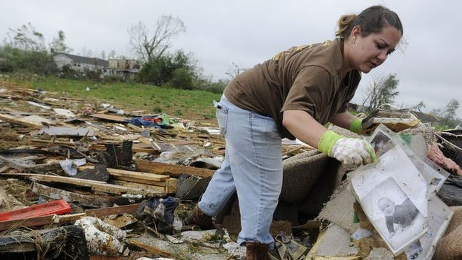 Dana Davis finds photographs in the wreckage of her home on Price Lane where a tornado caused heavy damage Tuesday, April 29, 2014 in Fayetteville, TN.