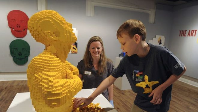 """Corbin Thornbury,10, who has been blind since birth, examines his favorite art piece Saturday morning at the the """"Art of the Brick"""" Lego exhibit as Cortlandt Glover, Director of Education at the Pensacola Museum of Art looks on. Artist Nathan Sawaya was contacted and told Nathan's story and gave permission for Nathan to touch the art."""
