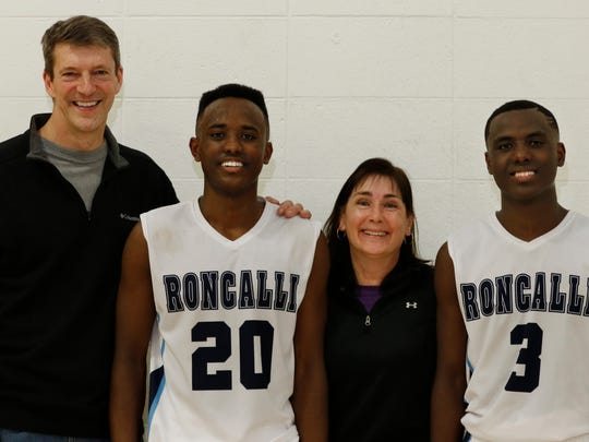 Mike and Mary Lambert pose for a photo with their sons Tomerot, left, and Chombi after the Roncalli vs. Valders game on Thursday. The brothers were adopted from Ethiopia in 2004.