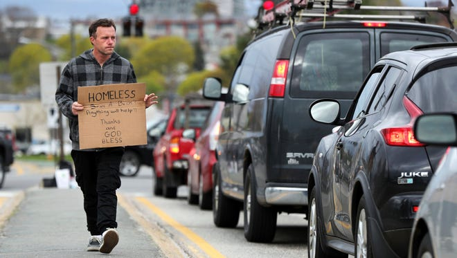 Derek Cote, a homeless man, panhandles in the median strip on a street in Portland, Maine, on May 10, 2017. The city recently began a program to offer day jobs cleaning up parks and other light labor jobs to panhandlers for $10.68 an hour.