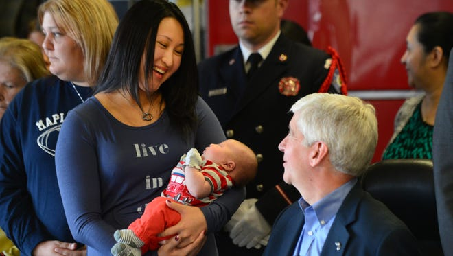 Kate Rodeman talks with Gov. Rick Snyder while holding her son, Blake, during a ceremonial bill signing to rename a portion of Business I-96 in honor of  Dennis Rodeman, who was struck by a car and killed while collecting donations for a charity in September.